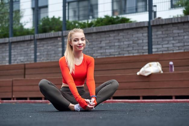 Sportsmenka robi ćwiczenia rozciągające nogi z piłką lekarską. dopasuj kobieta ćwiczenia z piłką w siłowni treningu.