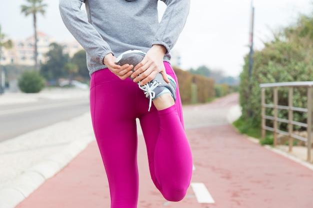 Sportsmenka rozciągająca mięśnie czworogłowe
