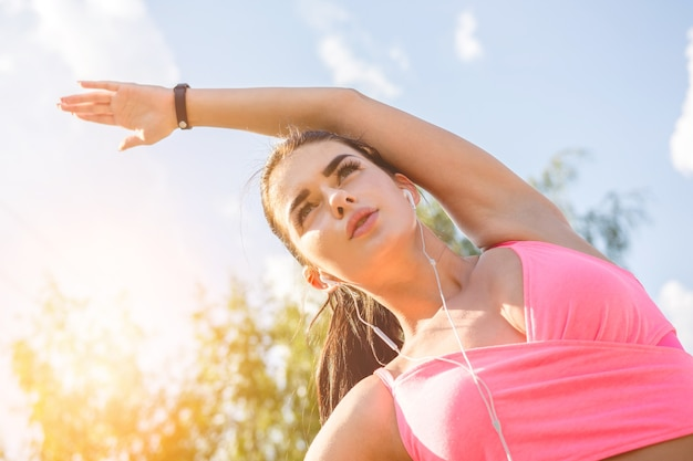 Sportsmenka rozciągająca się na słonecznym tle