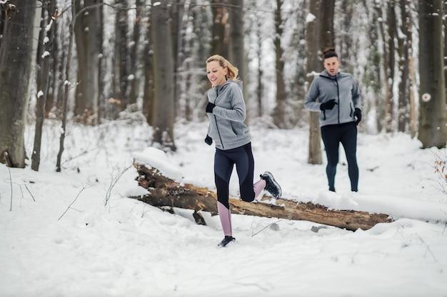 Sportsmenka ściga się ze swoim przyjacielem w lesie w śnieżny zimowy dzień. fitness razem, fitness na świeżym powietrzu, fitness zimowy