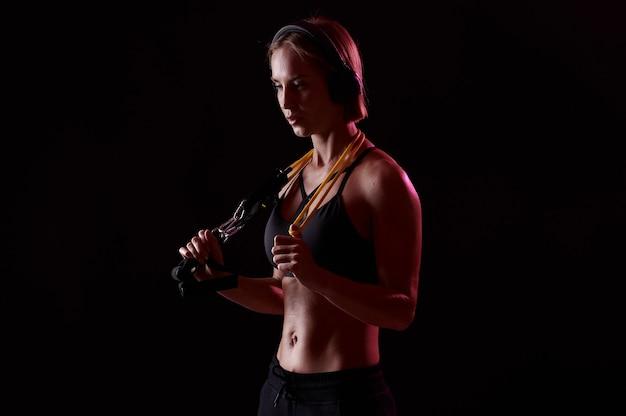 Sportsmenka trenująca z taśmami oporowymi na czarnym tle i słuchająca muzyki w słuchawkach