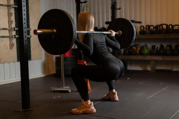Sportsmenka w czarnym dresie i beżowych trampkach wykonuje na siłowni przysiady ze sztangą.