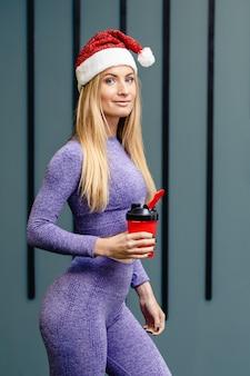 Sportsmenka w kapeluszu santa trzyma butelkę wody