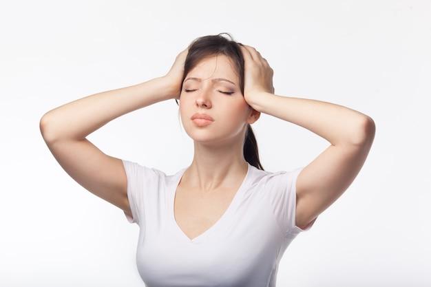 Sportsmenka z bólem głowy, trzymając głowę na białym tle