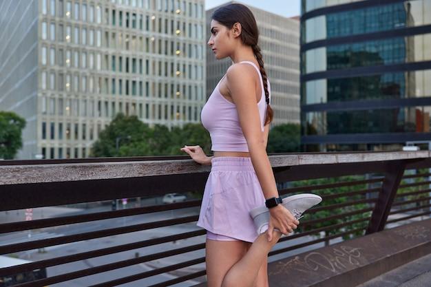 Sportsmenka z warkoczem rozgrzewa się przed ćwiczeniami joggingowymi podnosi nogę ubrana w stroje sportowe pozuje na moście podziwia widoki na miasto z góry będąc w dobrej formie fizycznej