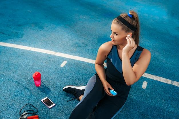 Sportsmenka za pomocą słuchawek dousznych