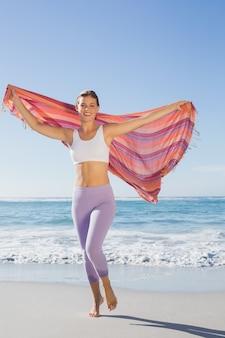 Sporty blondynki pozycja na plaży z szalikiem