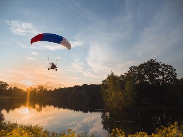 Sporty ekstremalne. zasilany spadochronem wieczorem na tle błękitnego nieba