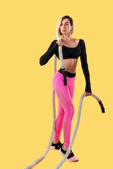 Sporty kobieta odpoczywa po treningu z arkanami. fotografia blondynki kobieta w różowym i czarnym sportswear na kolor żółty ścianie. siła i motywacja.