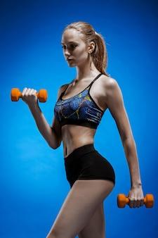 Sporty kobieta robi aerobikowi ćwiczenie z czerwonymi dumbbells