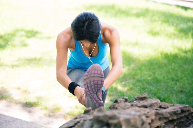 Sporty kobieta rozciąganie nóg w parku