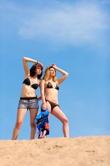Sporty kobiety stoi w piasku patrzeje daleko od w odległości