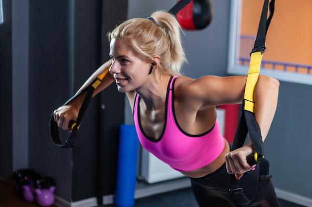 Sporty kobiety trenujące z pasami fitness trx na siłowni. treningowe pasy do zawieszania.