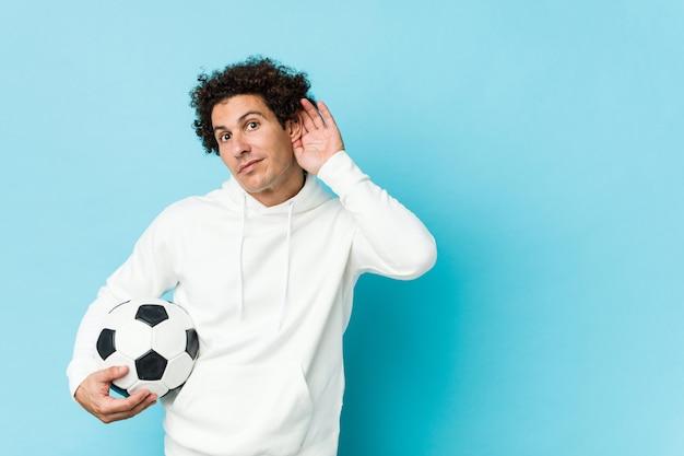 Sporty mężczyzna trzyma piłki nożnej piłkę próbuje słuchać plotki.