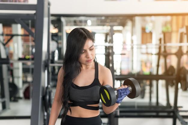Sporty młoda azjatycka kobieta z dumbbell