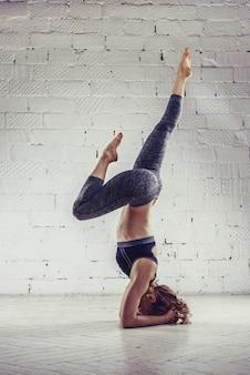 Sporty młoda kobieta robi joga praktyce odizolowywającej na białym tle