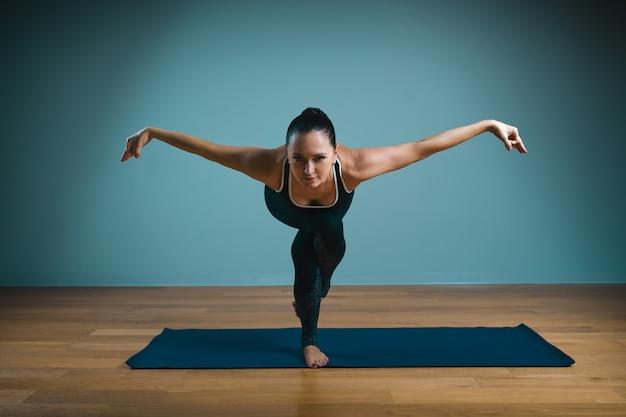 Sporty młoda kobieta robi rozciąganie. szczupła dziewczyna praktykuje jogę w pomieszczeniu na niebieskiej ścianie. spokój, relaks, koncepcja zdrowego stylu życia.