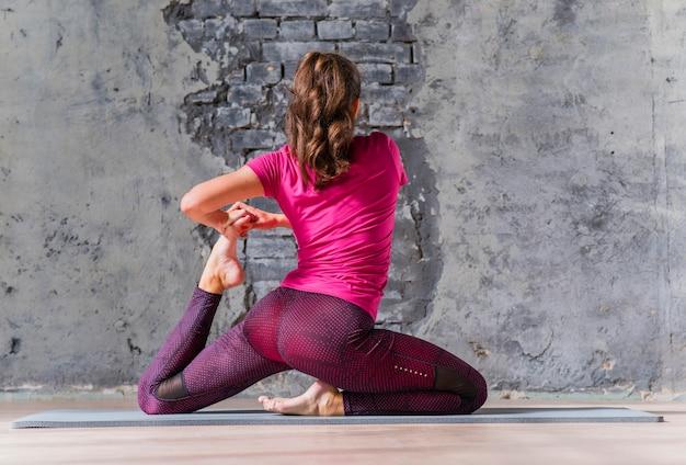 Sporty młoda kobieta w sportswear pracującym out indoors