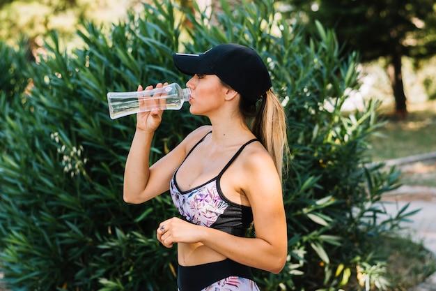 Sporty młodej kobiety pozycja blisko rośliny pije wodę od butelki