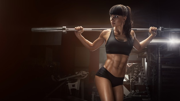 Sporty seksowna kobieta robi kucającemu treningowi w gym