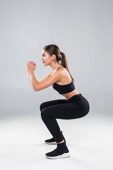 Sporty sportowa kobieta kucanie robi przysiadom w gym odizolowywającym nad biel ścianą