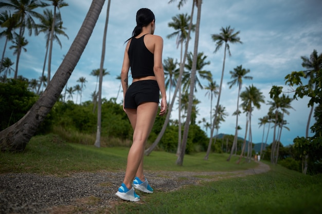 Sporty sprawności fizycznej kobiety bieg przy tropikalnym parkiem