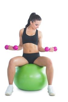 Sporty szczupła kobieta trenuje jej ręki z dumbbells siedzi na ćwiczenie piłce