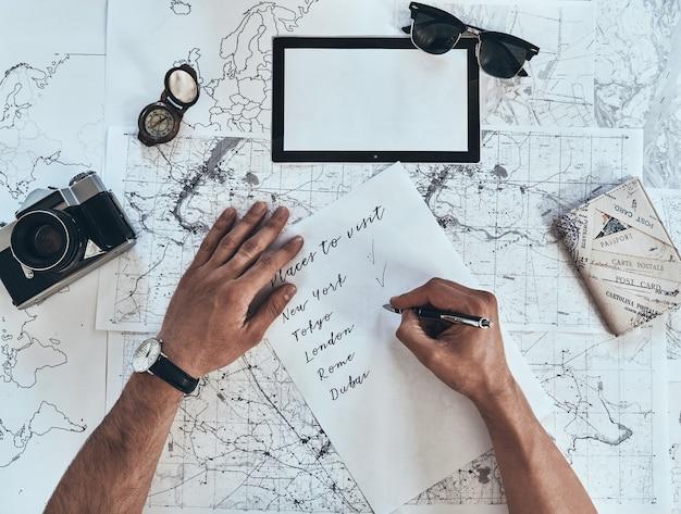 Sporządzenie listy. bliska widok z góry mężczyzny spisującego listę kontrolną z okularami przeciwsłonecznymi, aparatem fotograficznym