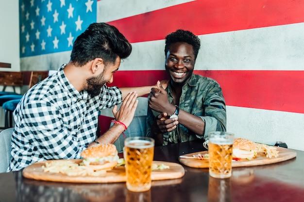 Spotkaj się po pracy. dwóch uśmiechniętych chłopców bawi się spędzając czas z przyjaciółmi w pubie i pijąc piwo.