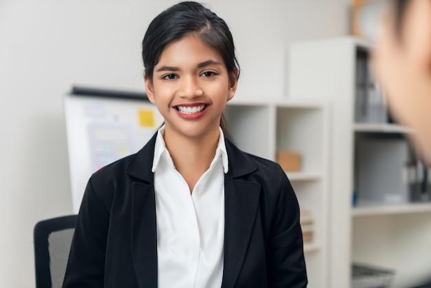 Spotkanie atrakcyjne bizneswoman azjatyckiego i rozmowa z burzą mózgów na temat planowania pracy zespołowej na stole z laptopem w biurze