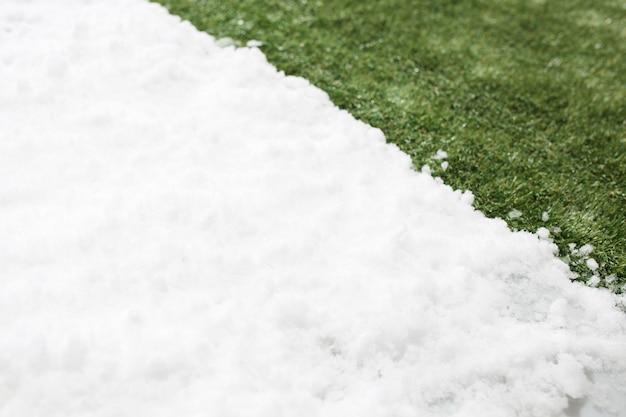 Spotkanie biały śnieg i zielona trawa z bliska. między zimowym a wiosennym tłem koncepcji.