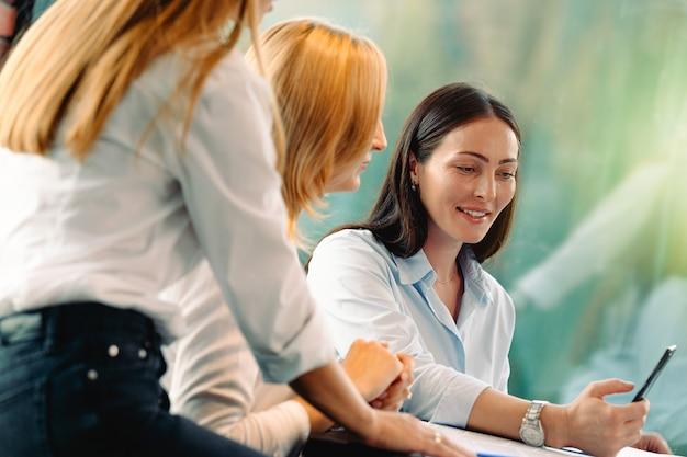 Spotkanie biznesowe. kobiety siedzą przy stole przed oknem. pani pokazuje informacje dla biznesu na smartfonie. zakupy online, przelewy, bankowość internetowa, praca na odległość.