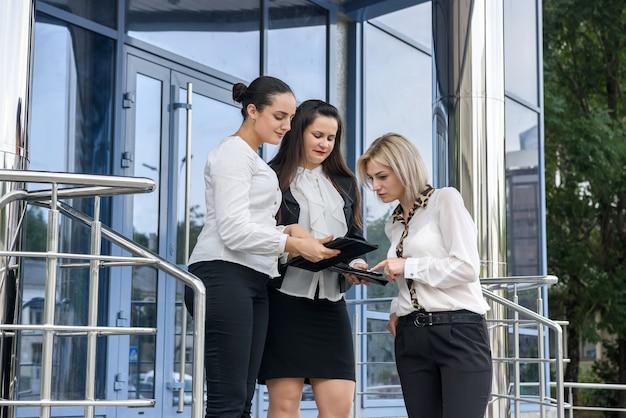 Spotkanie biznesowe na zewnątrz budynku. trzy młode panie w garniturach omawiających informacje na tablecie