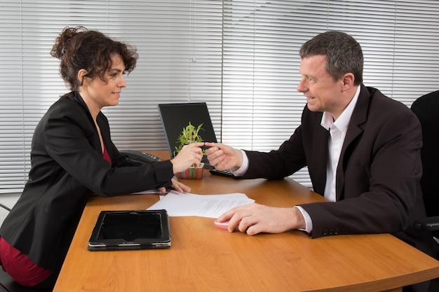 Spotkanie biznesowe: profesjonalny sukces zespołu; mężczyzna i kobieta rozmawiają ze sobą, patrząc na dokument