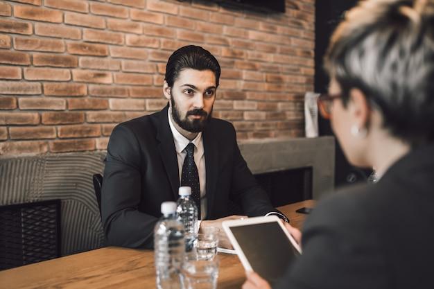 Spotkanie biznesowe. przystojny młody mężczyzna przeprowadza rozmowę kwalifikacyjną.