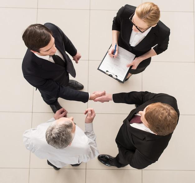 Spotkanie biznesowe. widok z góry na cztery osoby w strojach formalnych stojących blisko siebie, podczas gdy dwie z nich ściskają dłonie