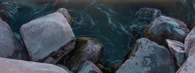Spotkanie błękitnej wody oceanu z kamieniami na plaży. wysokiej jakości zdjęcie