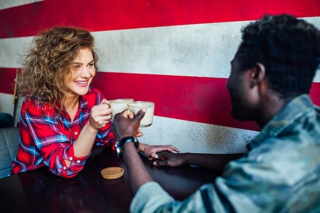 Spotkanie dwóch studentów, picie latte i dobra zabawa. studenci podczas przerwy w kawiarni.