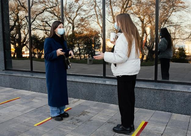 Spotkanie dziewczyn przy kawie w maskach