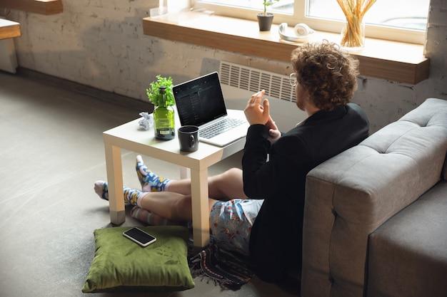 Spotkanie konferencyjne mężczyzna bez spodni, ale w kurtce, pracujący na laptopie komputerowym