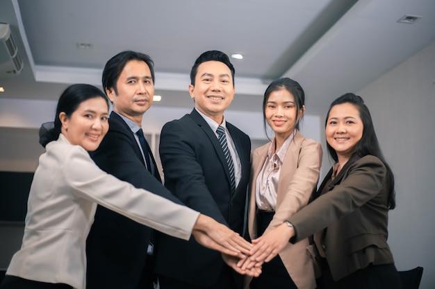 Spotkanie korporacyjne koncepcja pracy zespołowej, ludzie biznesu łączący się za ręce, zespół startowy