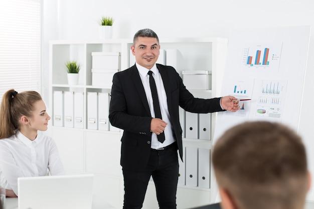 Spotkanie ludzi biznesu w biurze w celu omówienia projektu. dorosły biznesmen, wskazując na diagramie. sukces biznesowy i koncepcja pracy zespołowej