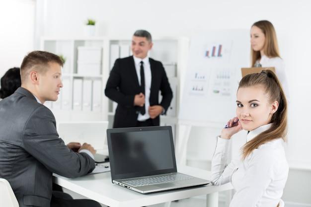 Spotkanie ludzi biznesu w biurze w celu omówienia projektu. młody ładny żeński pracownik biurowy z kolegami. koncepcja spotkania biznesowego i pracy zespołowej