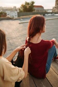 Spotkanie marzycieli na dachu. dziewczyna splata włosy koleżanki. wypoczynek i hobby młodzieży, beztroska rozrywka