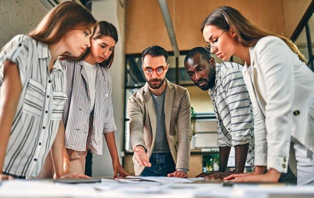 Spotkanie pracowników. grupa młodych, nowoczesnych ludzi w eleganckim codziennym stroju dyskutuje o czymś podczas pracy w kreatywnym biurze.