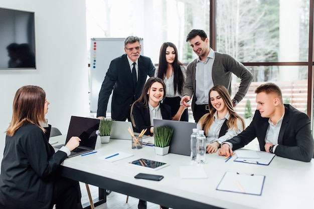 Spotkanie pracowników. grupa młodych nowoczesnych ludzi w eleganckim stroju casual, omawiając coś podczas pracy w kreatywnym biurze. czas biznesu.