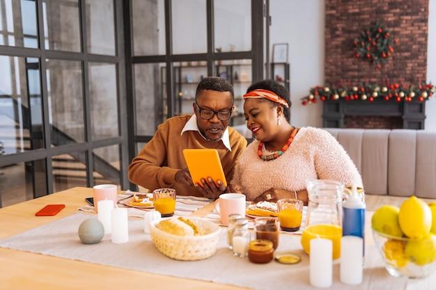 Spotkanie rodzinne. pozytywna radosna kobieta siedzi razem z bratem, patrząc na ekran tabletu