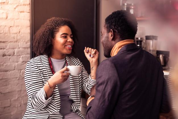 Spotkanie rodzinne. radosna miła kobieta patrząc na swojego brata podczas rozmowy z nim
