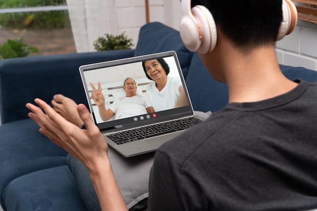 Spotkanie wideokonferencji azjatyckiego mężczyzny z chorym starszym ojcem, aby zachęcić i zapytać o chorobę. koncepcja technologii komunikacyjnej,