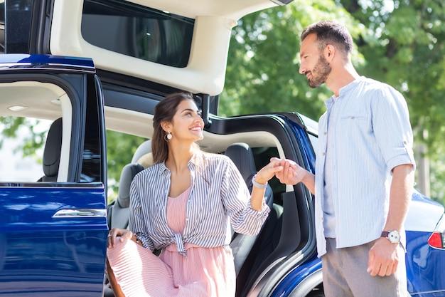 Spotkanie z mężem. żona czuje się szczęśliwa widząc, jak jej przystojny mąż spotyka ją w pobliżu samochodu